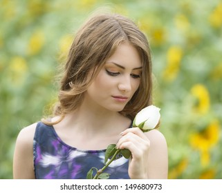 Romantic woman with rose lying on sunflowers field