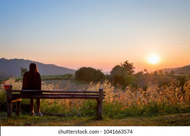 Romantic woman sitting on the wooden chair.Asian girl looking at sunrise in the morning on mountain ,Suphanburi province,Thailand.Lonely girl with nature concept.