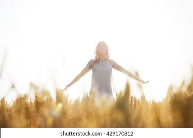 romantic woman taking a deep breath in the wheat