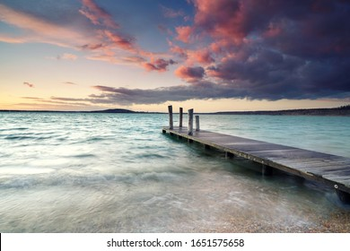 romantic wooden jetty on the beach, magical light at sunset in spring