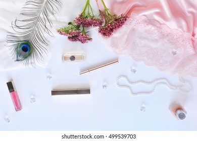 Romantic workspace with pink flowers, peacock feather, cosmetics and silk on white background. Flat lay composition of boudoir. Glamor top view.