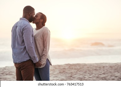 Romantic young African couple standing together on a sandy beach at sunset holding hands and kissing each other
