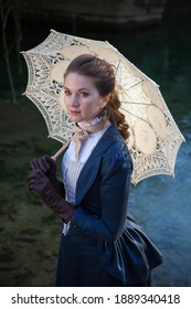 Romantic young beautiful lady walking outdoors with open umbrella. Victorian style vintage