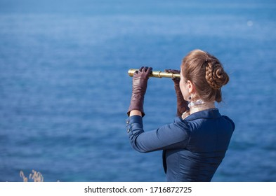 Romantic young beautiful lady wearing victorian dress looking at spyglass seascape. Vintage style. Steampunk concept