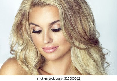 Romantic young blonde woman with closed eyes. Fashion photo. Girl with long healthy hair and perfect makeup. Studio shot.