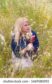 Romantic young blonde woman holding red poppy flowers in a field with high grasses