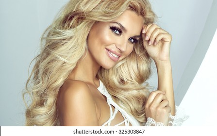 Romantic young blonde woman looking at camera. Fashion photo. Girl with long healthy hair and perfect makeup. Studio shot.