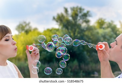 Romantic young bride and groom blowing bubbles as they celebrate their recent marriage together outdoors in nature, close up of their faces and the bubbles