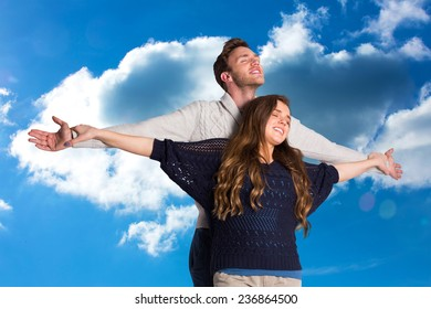 Romantic young couple with arms out against cloudy sky