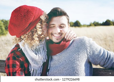 Romantic young couple of a beautiful blonde woman with curly hair and wearing a red wool cap kissing to her boyfriend and a handsome man outdoor