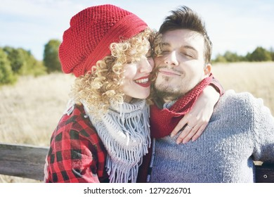 Romantic young couple of a beautiful blonde woman with curly hair and wearing a red wool cap hugs to her boyfriend and a handsome man outdoor