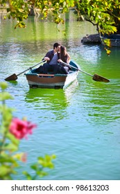 Romantic young couple boating on calm lake.