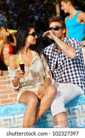 Romantic young couple by swimming pool having drinks, smiling.