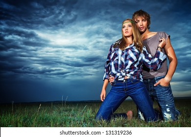 Romantic young couple in casual clothes sitting together in a field on a background of the storm sky.