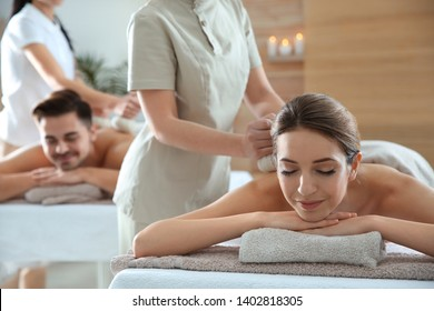 Romantic young couple enjoying herbal bag massage in spa salon
