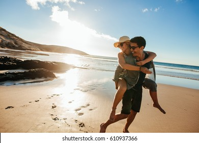 Romantic young couple enjoying summer holidays. Handsome young man giving piggyback ride to girlfriend on beach.