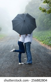 romantic young couple hiding behind the umbrella in the rain