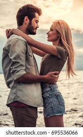 Romantic young couple is hugging, looking at each other and smiling while standing at the seaside