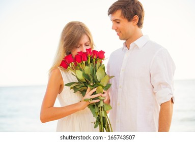Romantic Young Couple in Love, Man giving beautiful young woman red roses