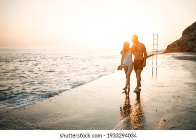 Romantic young couple in love walking together at sunset along the Mediterranean beach. Summer vacation in a warm country. Happy married couple on vacation in Turkey. Selective focus