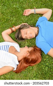 Romantic young couple lying on grass teenage love top view
