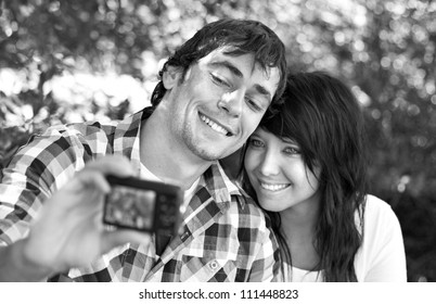 Romantic young couple posing for a self portrait with small pocket camera in hand