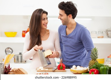 Romantic young couple preparing italian food at home.