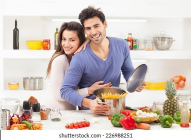 Romantic young couple preparing pasta at home.