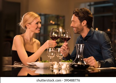 Romantic young couple at restaurant raising a toast. Beautiful couple with glasses of red wine in restaurant. Couple toasting wine glasses during a romantic dinner in a gourmet restaurant.