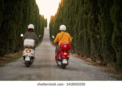 Romantic young couple riding on a scooter in old European on vacation. Back view.