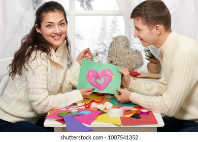 romantic young couple sit at the table and shows origami red heart, happy people and love concept