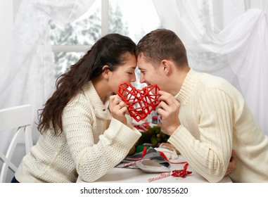 romantic young couple sit at the table and shows red heart, happy people and love concept