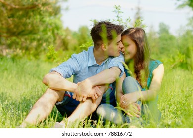 Romantic young couple sitting in a field