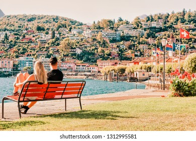 Romantic young couple sitting on bench at Ascona luxury tourist resort on Lake Maggiore in Ticino canton in Switzerland in summer. People outdoor street travel. Expensive family persons holiday.