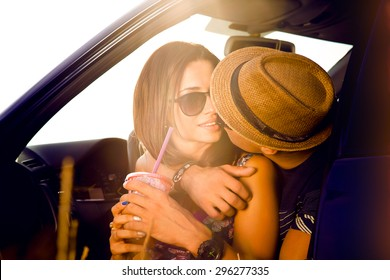 Romantic young couple sitting on the hood of their car while out on a roadtrip.Beautiful young woman kissing her boyfriend looking away smiling,outdoors.Car alongside coastal seashore bright sunlight