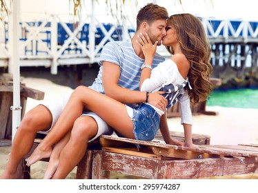 Romantic young couple together outdoors on summer day.Caucasian couple enjoying the beach view.Enjoy time together,lovely couple on the beach,kissing lops,party on beach,tan couple,fashionable outfit