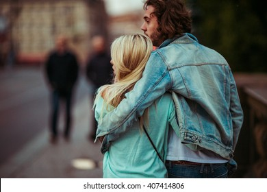 Romantic young couple walking & hugging in Prague street