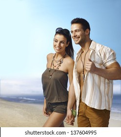 Romantic young couple walking on the beach hand in hand, smiling happy.