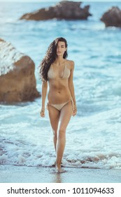 Romantic young girl in bikini outdoors against tropical background. Close-up portrait of beautiful sensual brunette mixed race Asian Caucasian woman walking fwom water on the beach. Slim female model