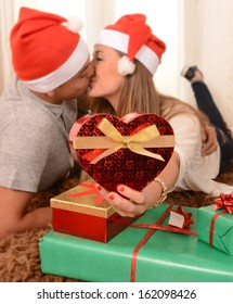 Romantic Young Happy Couple with Christmas Presents on rug at home