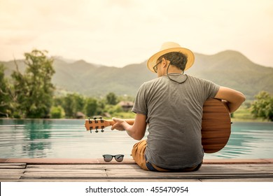 Romantic young man sitting on the pool at sunset with playing the guitar
