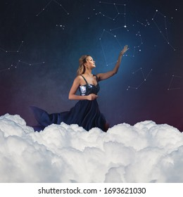 Romantic young woman in a blue dress against a blue sky aspires to the stars. dreamer girl sits on the clouds and stretches out her hand to the starry sky and constellations