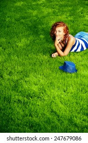 Romantic young woman lying on a green lawn at a park. Summer day.