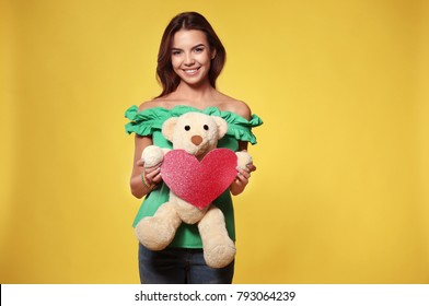 Romantic young woman with paper heart and toy bear for Valentine's Day on color background