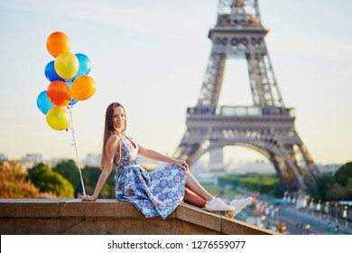 Romantic young woman in Paris with bunch of colorful balloons looking at the Eiffel tower