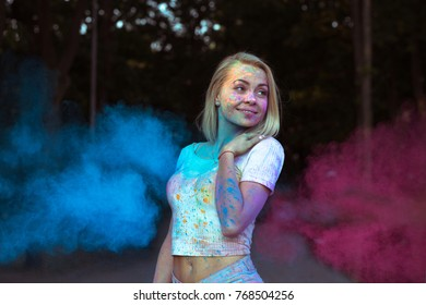 Romantic young woman posing with Holi powder exploding around her