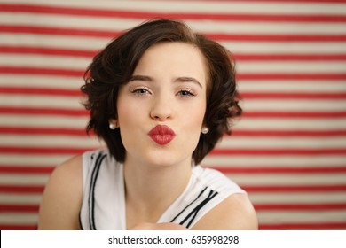 Romantic young woman puckering up her bright red lips for a kiss in a sensual gesture over a striped red and white blurred background