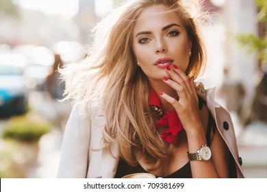 Romantic young woman with red manicure posing in sunny town after work. Close-up portrait of enchanting blonde lady in wristwatch wearing beige jacket in warm day.