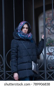Romantic young woman, in a scarf, posing on the background of a vintage wrought-iron gate in the courtyard of an old building. Winter day in the city.
