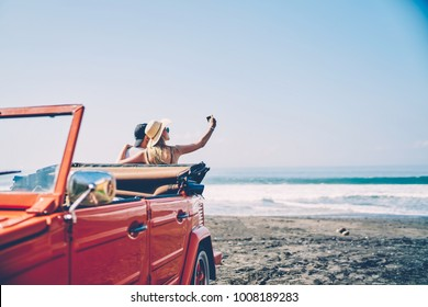 Romantica couple making photo on smartphone camera standing near vintage rental car on ocean beach enjoying summer vacation together, hipsters taking picture on cellular resting near sea on weekends
